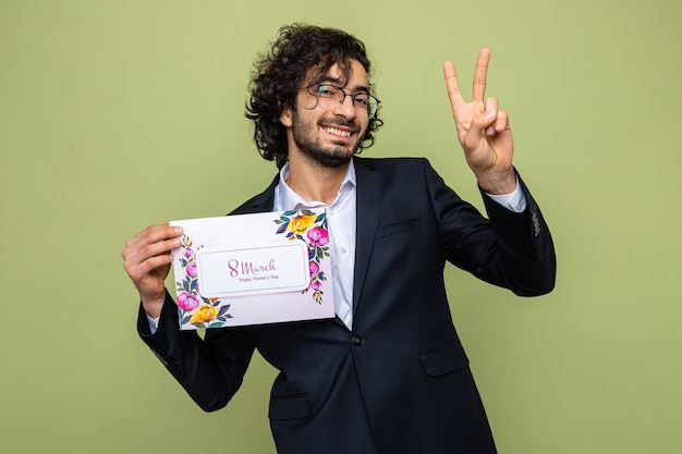 Knappe man in pak met een wenskaart die vrolijk lacht met een v-teken en internationale vrouwendag viert op 8 maart