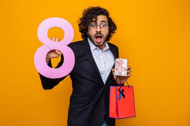 Knappe man in pak met huidige papieren zak met cadeau en nummer acht kijkend naar camera verrast en verbaasd vieren internationale vrouwendag 8 maart staande over oranje achtergrond