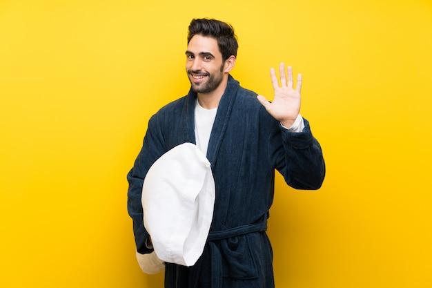 Knappe man in pyjama die met hand met gelukkige uitdrukking groeten