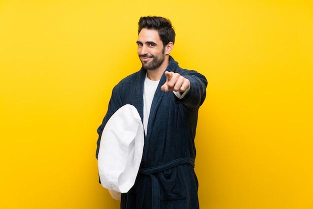 Knappe man in pyjama wijst vinger naar je met een zelfverzekerde uitdrukking