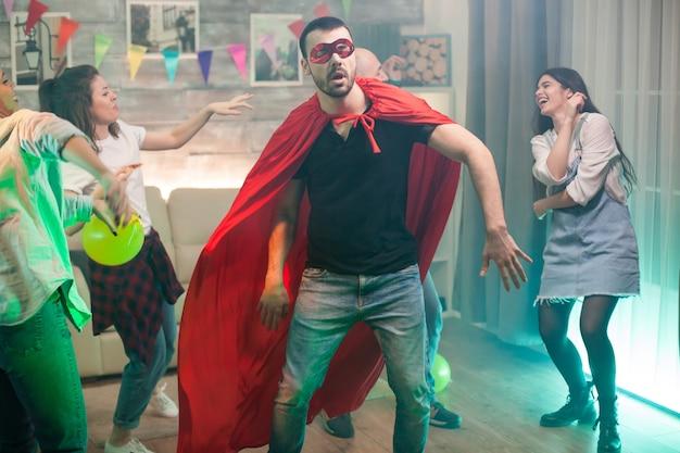 Knappe man in rood superheld kostuum feesten met zijn vrienden. vrolijke vrouw.