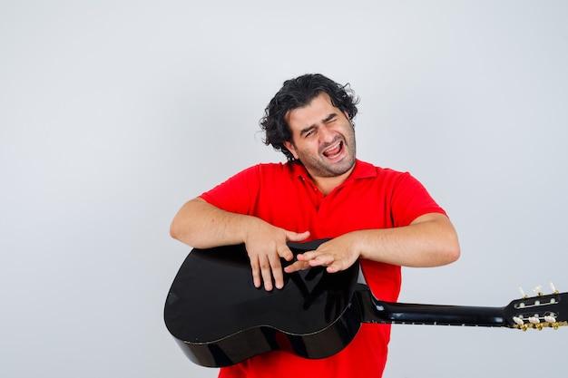 Knappe man in rood t-shirt kloppen op gitaar en vrolijk, vooraanzicht op zoek.