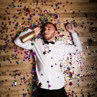 Knappe man in shirt met fles drank tussen confetti