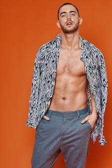Knappe man in shirt naakt torso poseren mode oranje achtergrond