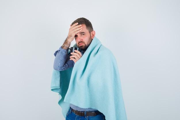 Knappe man in shirt, spijkerbroek, sjaal met kopje thee, hoofdpijn en op zoek uitgeput, vooraanzicht.