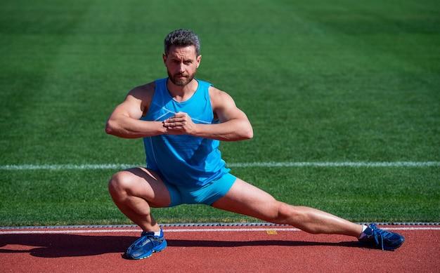 Knappe man in sportkleding die zich uitstrekt terwijl hij buiten opwarmt, flexibiliteit.