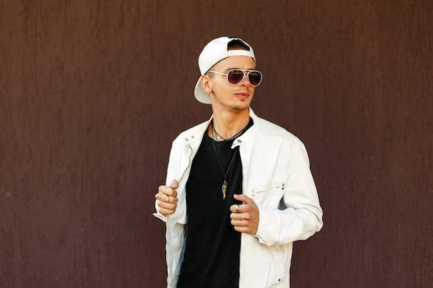 Knappe man in stijlvolle zonnebril in een modieus jasje met een baseballpet in de buurt van de muur