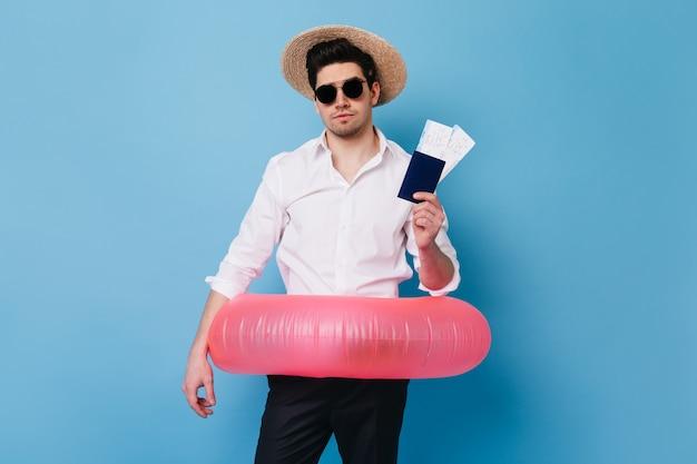 Knappe man in strooien hoed toont paspoort en vliegtickets. portret van een man in zakelijke kleding met opblaasbare cirkel.