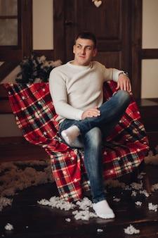 Knappe man in trui en spijkerbroek zittend op bankje over geruite deken met namaaksneeuw verspreid over de vloer