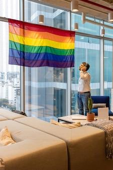 Knappe man in vrijetijdskleding, nadenkend over de vlag die de lgbt-gemeenschap vertegenwoordigt