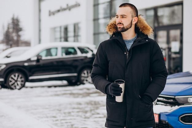 Knappe man in warme jas permanent met auto bedekt met sneeuw en koffie drinken