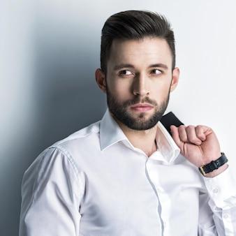 Knappe man in wit overhemd houdt het zwarte pak - poseren over muur. aantrekkelijke man met mode-kapsel. zelfverzekerde man met korte baard. volwassen jongen met bruin haar.