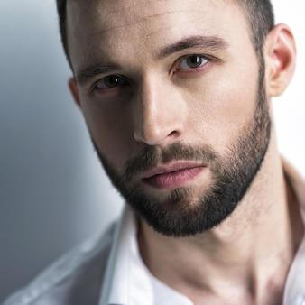 Knappe man in wit overhemd, poseren. aantrekkelijke man met mode-kapsel. zelfverzekerde man met korte baard. volwassen jongen met bruin haar. close-up portret.