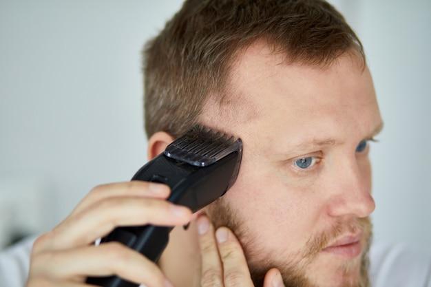 Knappe man in wit t-shirt snijden baard met trimmer thuis