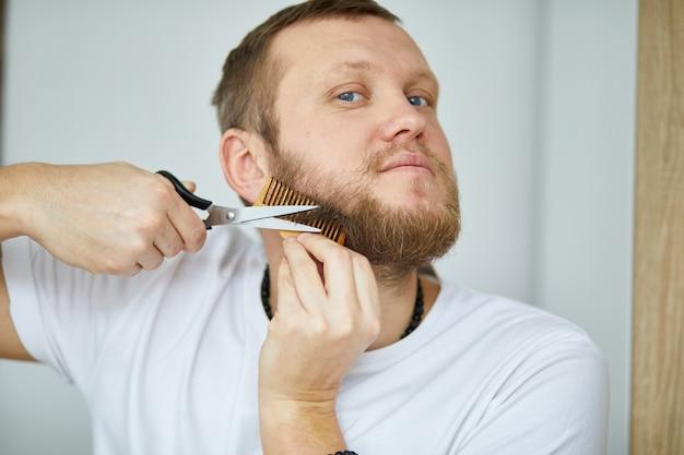 Knappe man in witte t-shirts die baard knippen, snor persoonlijk zelf