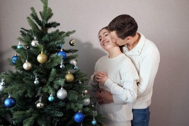 Knappe man in witte trui staat achter dame en kussen. paar versieren kunstmatige kerstboom close view