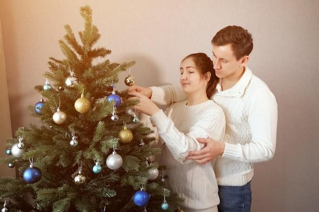 Knappe man in witte trui staat achter dame helpt bij het versieren van kunstmatige kerstboom van dichtbij