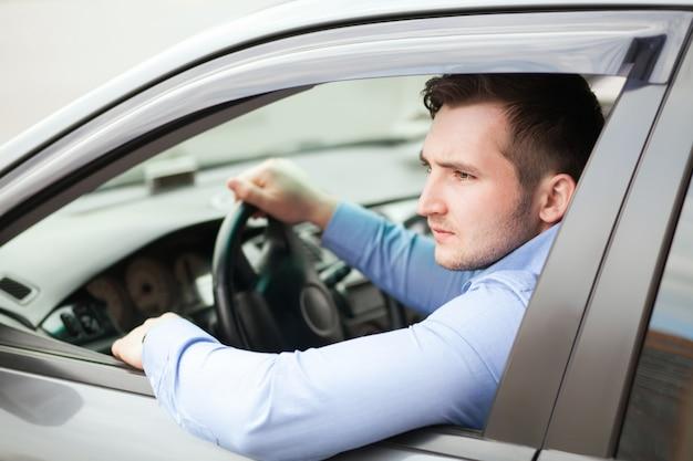 Knappe man in zijn nieuwe auto