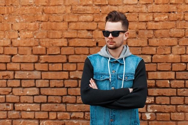 Knappe man in zonnebril en een denim gilet in de buurt van een bakstenen muur