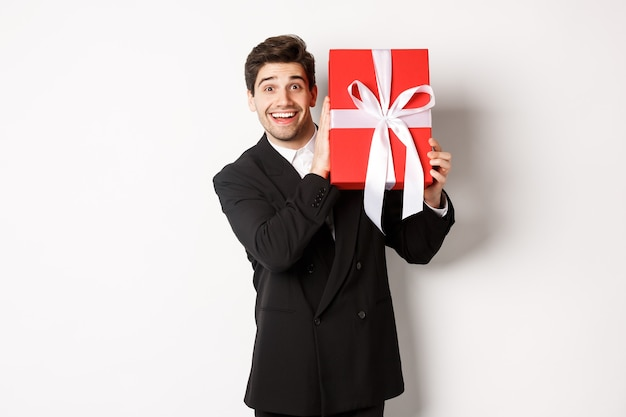 Knappe man in zwart pak, kerstcadeau ontvangen, verbaasd glimlachen, staande tegen een witte achtergrond.