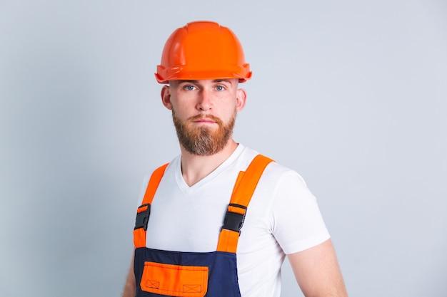 Knappe man ingenieur bij het bouwen van een beschermende helm op een grijze muur met een serieus gericht gezicht