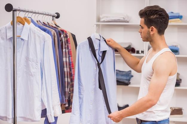 Knappe man kiezen stropdas aan het shirt in de kleedkamer.