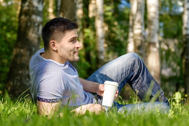 Knappe man koffie drinken in park