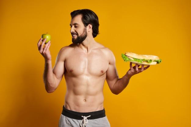 Knappe man maakt kiezen tussen appel en sandwich.
