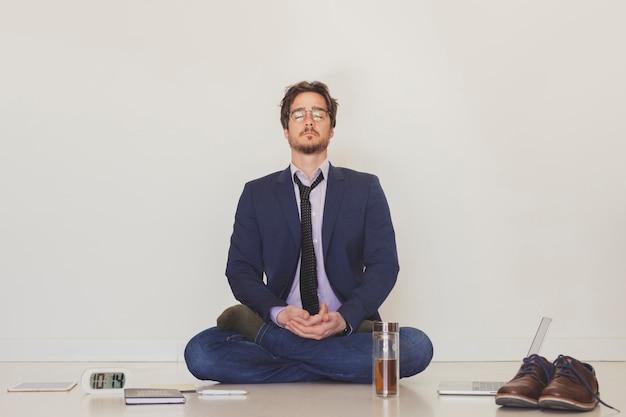 Knappe man mediteren op de vloer