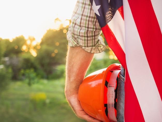 Knappe man met amerikaanse vlag tegen de achtergrond van bomen, blauwe lucht en zonsondergang. uitzicht vanaf de achterkant. arbeids- en werkgelegenheidsconcept