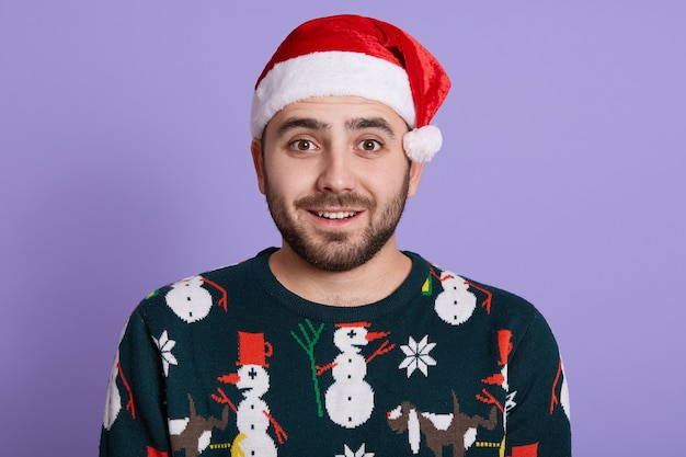 Knappe man met baard dragen kerstman hoed en grappige trui staan met glimlach en grote ogen op paars