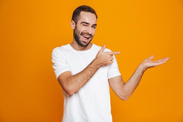 Knappe man met baard en snor copyspace op palm tonen terwijl staande, geïsoleerd op geel
