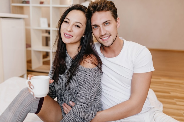 Knappe man met baard europese vrouw zachtjes omhelzen terwijl ze koffie drinkt