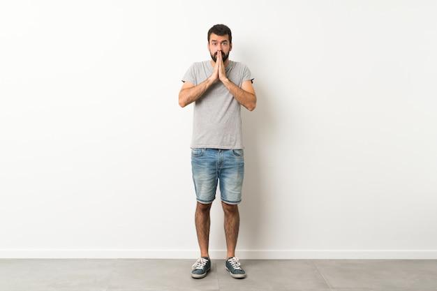Knappe man met baard houdt palm bij elkaar. persoon vraagt om iets