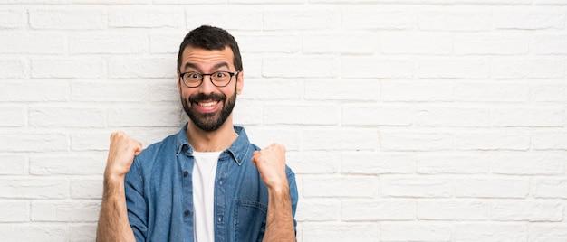 Knappe man met baard over witte bakstenen muur die een overwinning in winnaarpositie viert