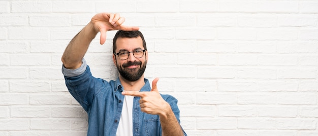 Knappe man met baard over witte bakstenen muur gericht gezicht. framing symbool