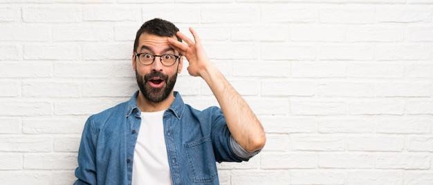 Knappe man met baard over witte bakstenen muur heeft net iets gerealiseerd en heeft de oplossing voor ogen