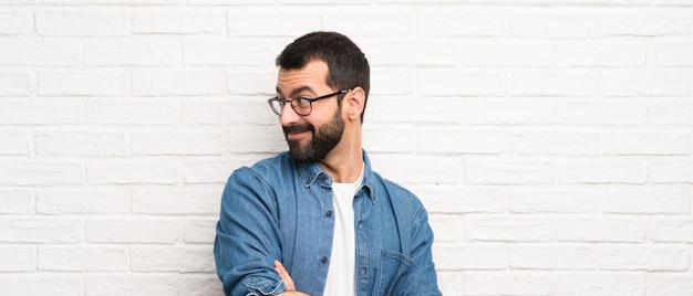 Knappe man met baard over witte bakstenen muur met gekruiste en gelukkige wapens