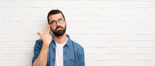 Knappe man met baard over witte bakstenen muur met problemen die zelfmoordgebaar maken