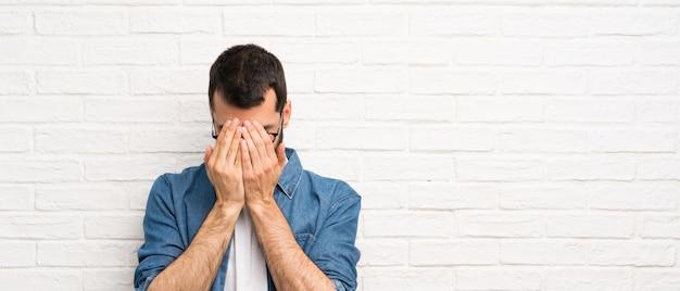 Knappe man met baard over witte bakstenen muur met vermoeide en zieke uitdrukking