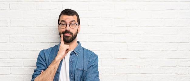 Knappe man met baard over witte bakstenen muur op zoek naar voren