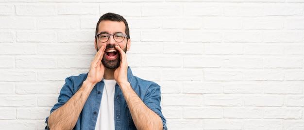 Knappe man met baard over witte bakstenen muur schreeuwen en aankondiging van iets
