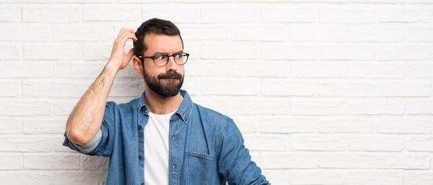 Knappe man met baard over witte bakstenen muur twijfels terwijl hoofd krabben