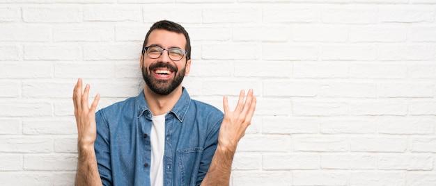 Knappe man met baard over witte bakstenen muur veel glimlachen