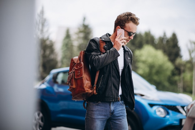 Knappe man met behulp van de telefoon door de auto