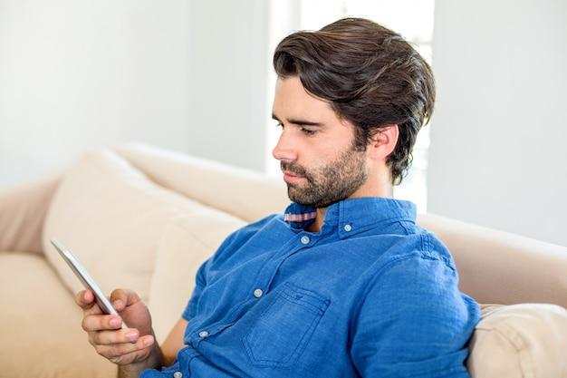 Knappe man met behulp van mobiele telefoon thuis