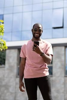 Knappe man met behulp van moderne smartphone buitenshuis