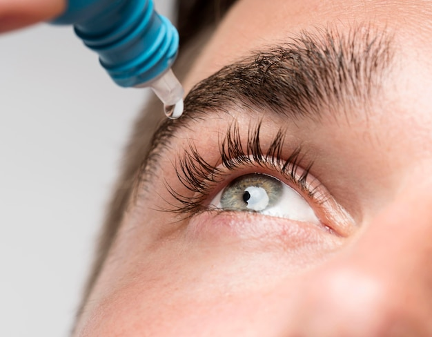 Knappe man met behulp van oogdruppels close-up