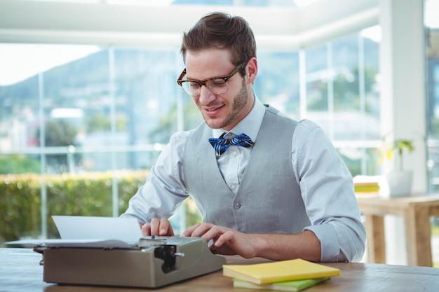 Knappe man met behulp van ouderwetse typemachine in heldere kantoor