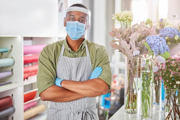 Knappe man met beschermend masker en handschoenen voor het verkopen van boeketten tijdens pandemie